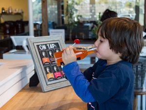 Young kombucha fan taking a sip at the kombucha mini bar located inside Ferm Farm. (Grant Geipel)