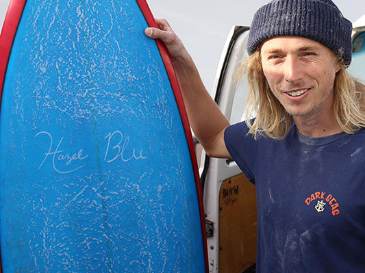 Hansen showing off the first board he created start to finish, titled after his daughter.