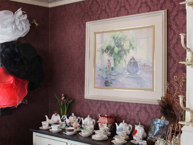 Multiple tea hats and porcelain tea sets arranged in the dining room. (Celeste Espinoza)